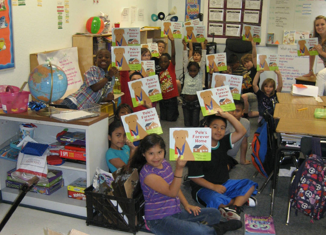 Blackburn Elementary School kids hold up their copies of Pele's Forever Home